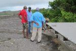 Members repairing cracks to the water catchment tank